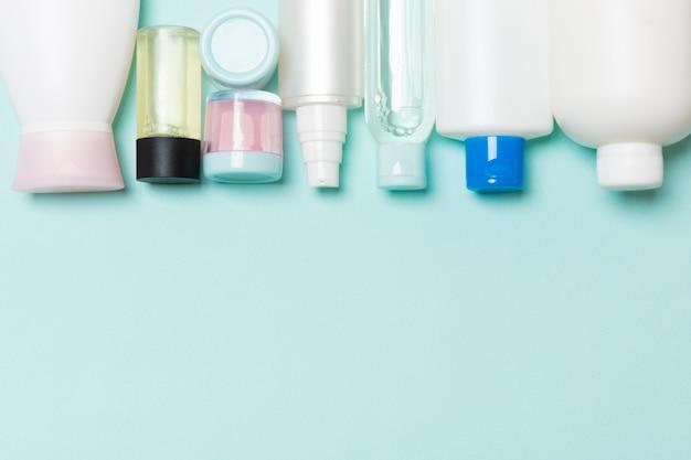 Vista superior de botellas de cosméticos sobre fondo azul.