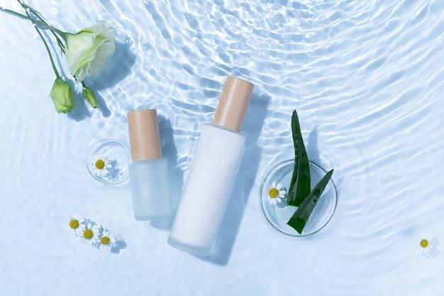 Vista superior de las botellas de cuidado de la piel sobre una superficie de agua azul claro con aloe vera y flores de margarita