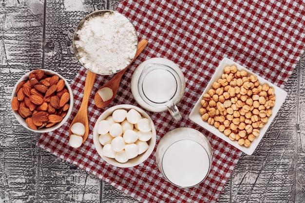 Vista superior botellas de leche con queso y cuchara de madera, almendras, avellanas sobre fondo de madera gris. horizontal