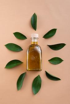 Vista superior de botellas llenas de aceite rodeadas de hojas