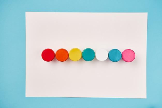 Vista superior de botellas de pintura color arco iris sobre lienzo blanco. concepto de orgullo lgbt foto de alta calidad