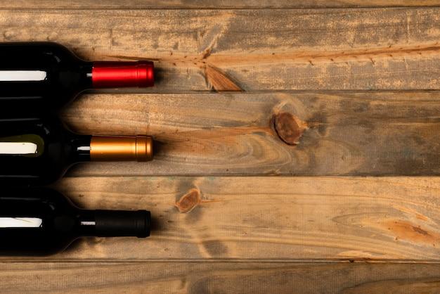 Vista superior de botellas de vino con fondo de madera