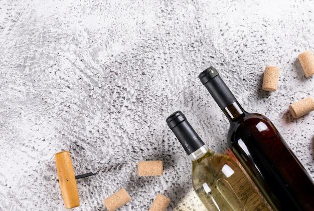 Vista superior de botellas de vino con tapones de corcho y copia espacio en piedra blanca horizontal