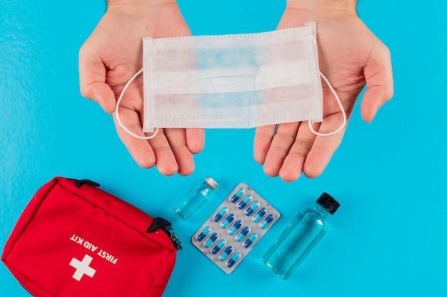 Vista superior del botiquín de primeros auxilios en las manos con máscara, vial, píldoras y botella. horizontal