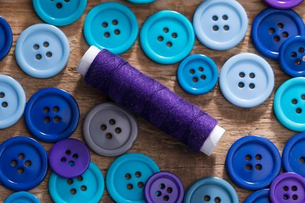 Vista superior de botones azules y carrete de hilo