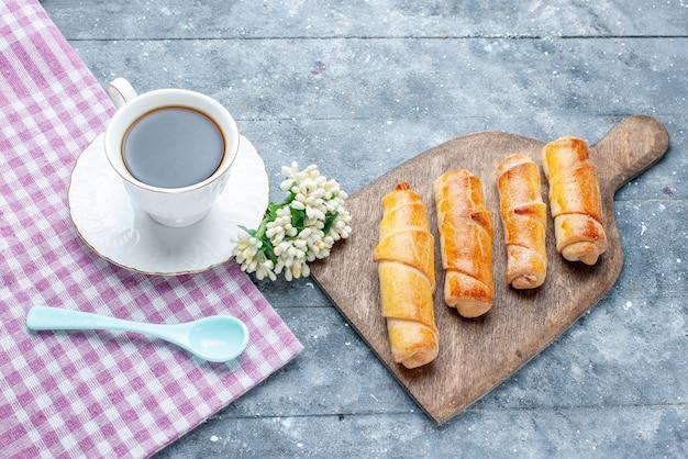 Vista superior brazaletes deliciosos dulces con relleno junto con una taza de café en la mesa de madera clara galleta de galleta de pastelería dulce de azúcar
