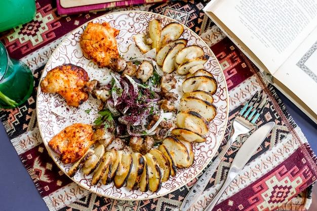 Vista superior brochetas de pollo con rodajas ‹papas, cebollas y hierbas espolvoreadas con zumaque