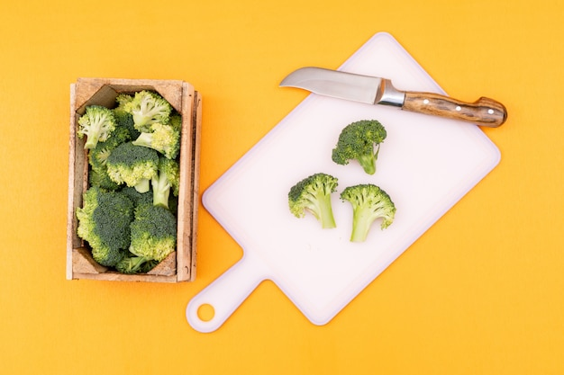 Vista superior de brócoli fresco en caja de madera junto a la tabla de cortar con un cuchillo sobre una superficie amarilla