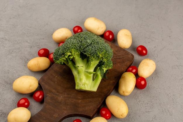 Vista superior de brócoli verde fresco junto con patatas tomates en el escritorio gris