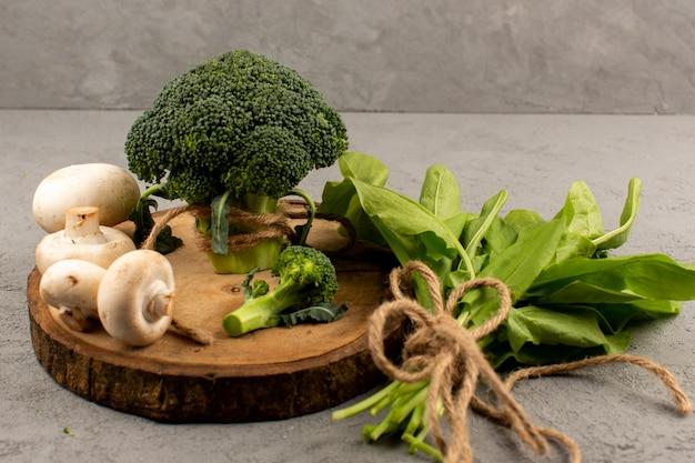 Vista superior de brócoli verde fresco maduro con champiñones sobre el fondo claro