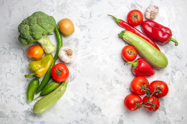 Vista superior de brócoli verde fresco con verduras en ensalada de mesa blanca salud madura