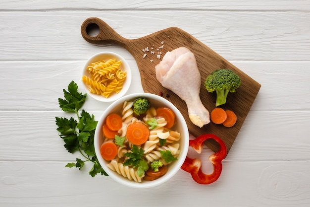 Vista superior de brócoli, zanahorias y fusilli en un tazón con muslo de pollo en la tabla de cortar