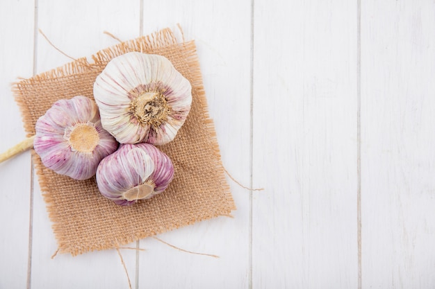 Vista superior de bulbos de ajo sobre tela de saco y superficie de madera