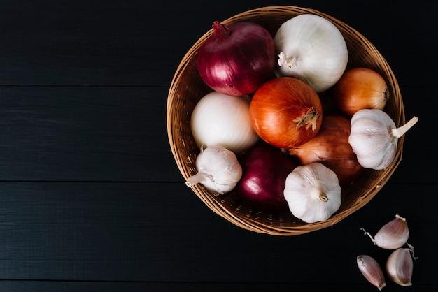 Vista superior de los bulbos y las cebollas del ajo en cesta en el contexto negro