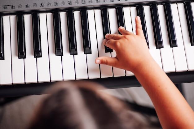 Vista superior de una cabeza y una mano de niñas tocando una melodía en un sintetizador electrónico