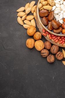 Vista superior de cacahuetes nueces frescas y otras nueces en superficie oscura