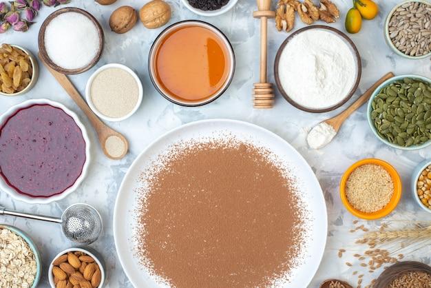 Vista superior de cacao en polvo en tazones de plato redondo con mermelada, miel, harina, semillas de calabaza, semillas de girasol, semillas de sésamo, almendras en la mesa
