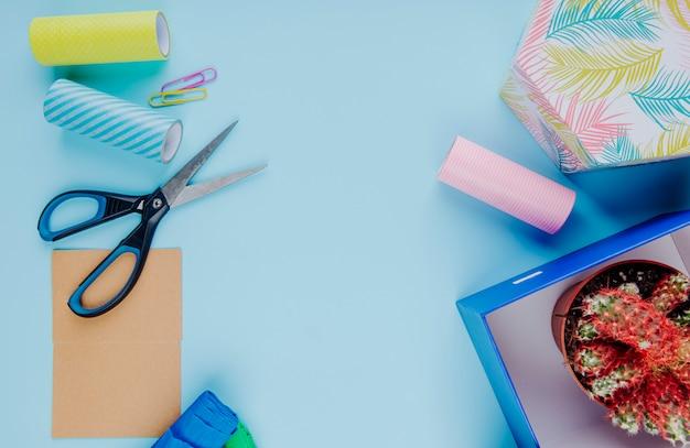 Vista superior de un cactus en una maceta en una caja de regalo de cartón con tijeras coloridos clips de papel y rollos de cinta adhesiva sobre fondo azul.