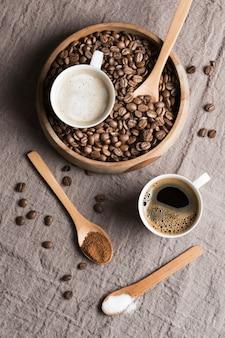 Vista superior de café y café con leche en tazas blancas con frijoles tostados