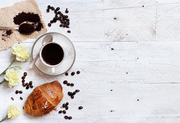 Vista superior de café con croissant en madera blanca rústica