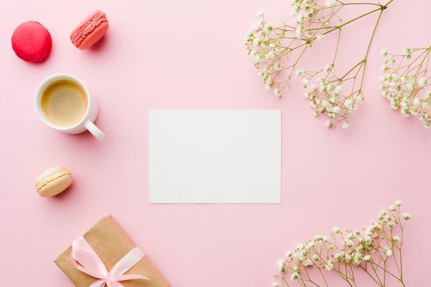 Vista superior de café con flores y papel blanco vacío