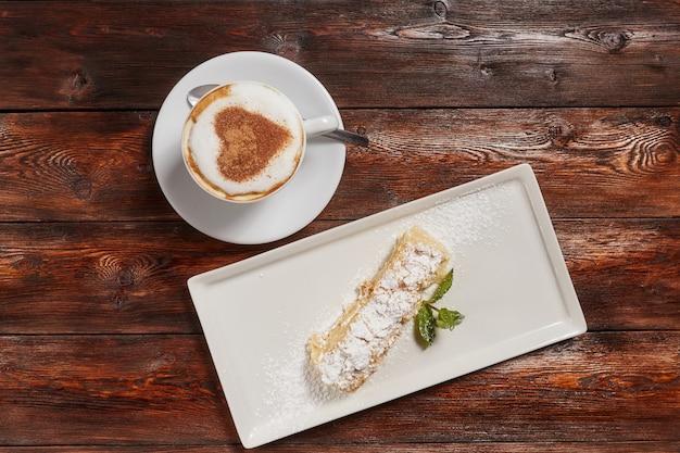 Vista superior café con leche arte con corazón, superficie de madera