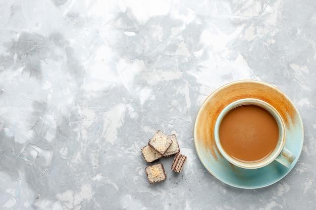 Vista superior de café con leche con gofres en el escritorio de luz, azúcar dulce, gofres, color leche