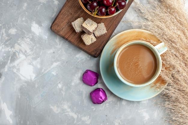 Vista superior de café con leche con gofres guindas frescas en el fondo claro galleta dulce azúcar hornear fruta