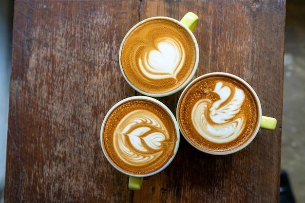 Vista superior de café con leche o café capuchino con hermoso árbol de arte latte en mesa de madera