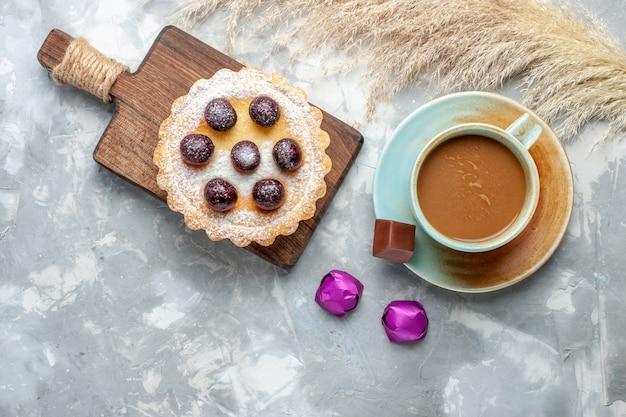 Vista superior de café con leche con pastel de cerezas en el color gris-blanco de la torta de escritorio con azúcar dulce hornear