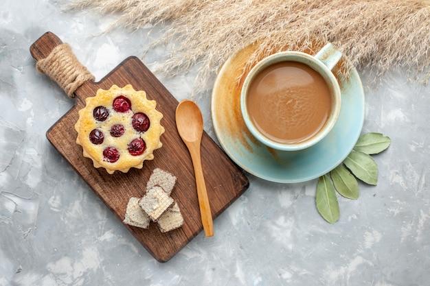Vista superior de café con leche con un pequeño pastel de cereza en la mesa de luz pastel galleta galleta dulce