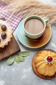 Vista superior de café con leche con tortas en mesa blanca pastel galleta azúcar dulce