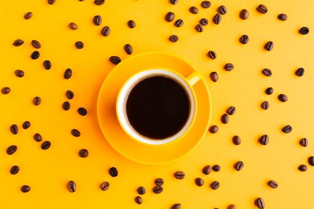 Vista superior de café negro rodeado de frijoles