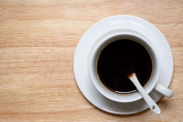 Vista superior de café negro en taza blanca sobre fondo de madera con espacio de copia.