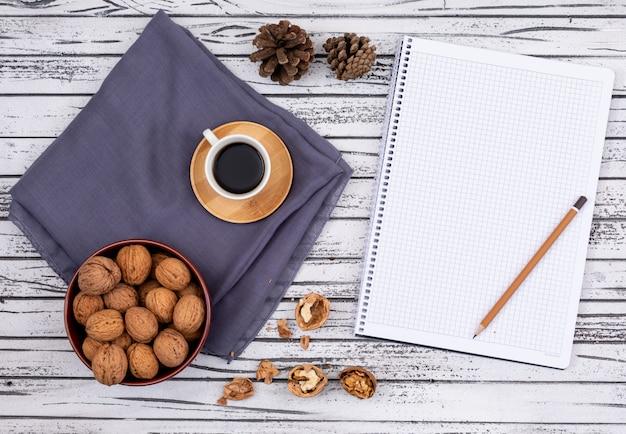Vista superior de café con nueces y copia espacio en el cuaderno sobre fondo blanco de madera horizontal