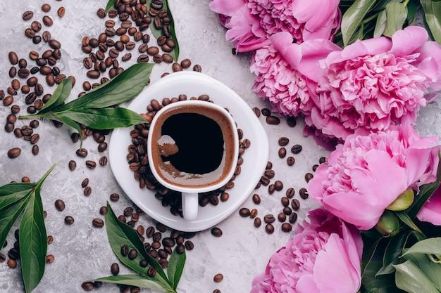 Vista superior de café y peonías en una mesa con granos de café