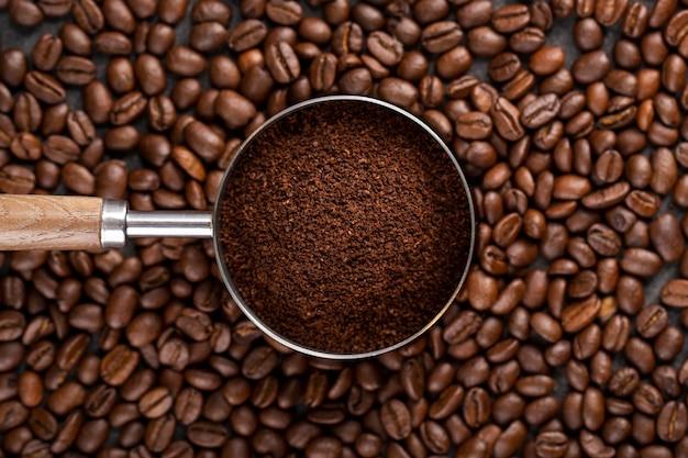 Vista superior de café en polvo en colador sobre granos de café