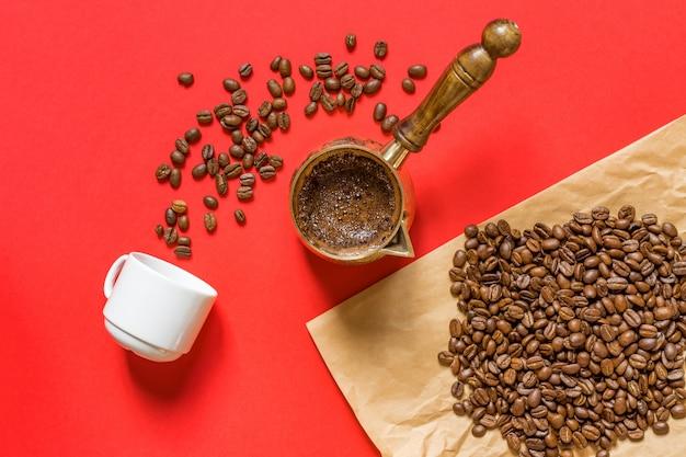 Vista superior de café recién preparado en cezve (cafetera tradicional turca), taza whte y granos de café sobre papel artesanal sobre fondo rojo.