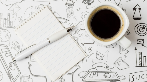 Vista superior café sobre papel lleno de garabatos