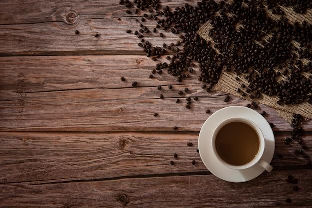 Vista superior de café en taza blanca y granos de café sobre fondo de madera con espacio de copia