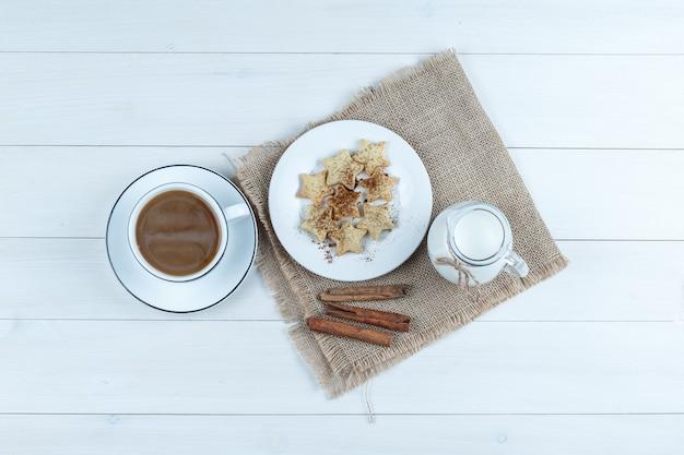 Vista superior de café en taza con galletas, canela, leche en madera y un pedazo de fondo de saco.