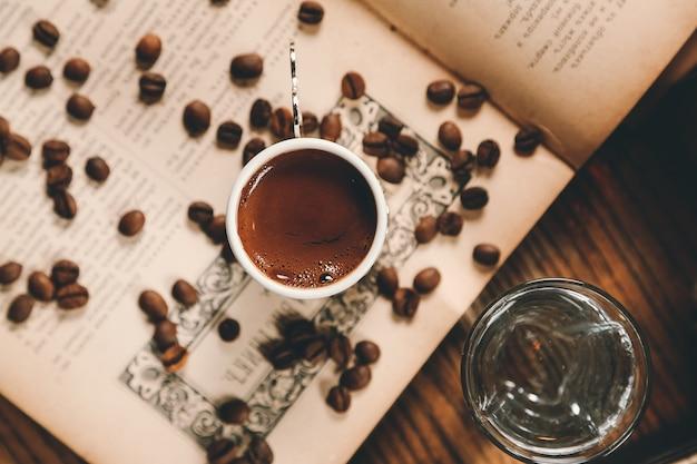 Vista superior de café turco con granos de café en un libro abierto con un vaso de agua