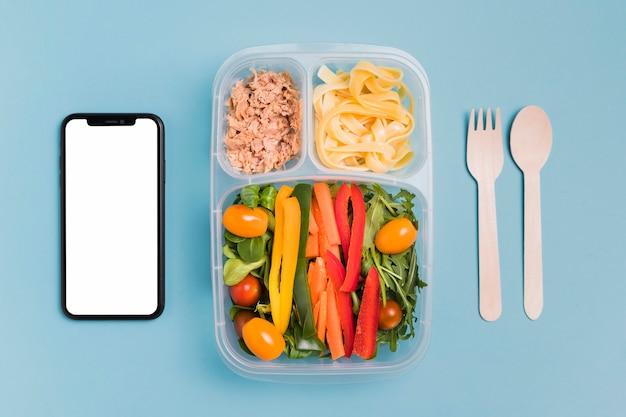 Vista superior caja de almuerzo de trabajo con teléfono en blanco