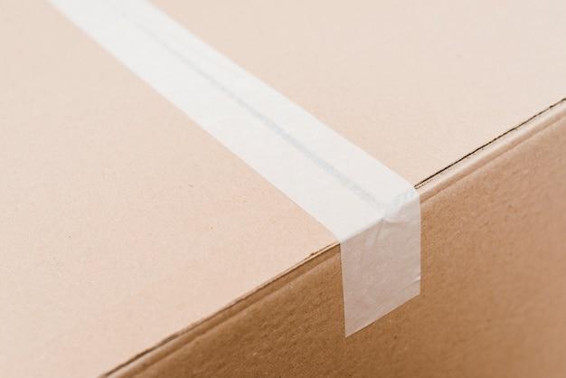 Vista superior de una caja de cartón sellada con cinta de embalaje blanca.