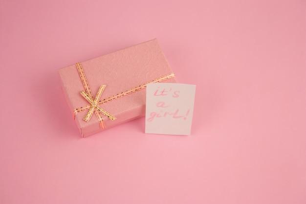 Vista superior de la caja de color rosa sobre fondo rosa y se nota, una niña