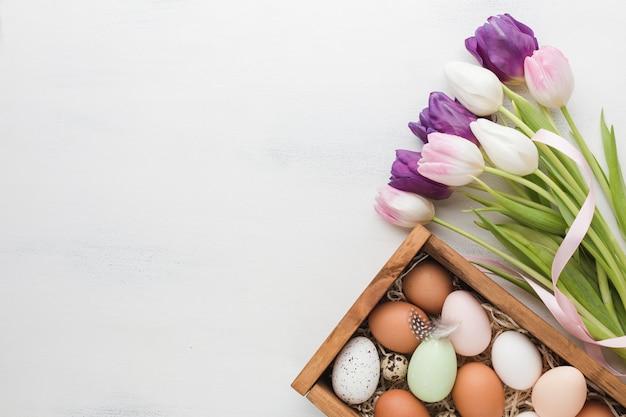 Vista superior de la caja con huevos para pascua y tulipanes multicolores