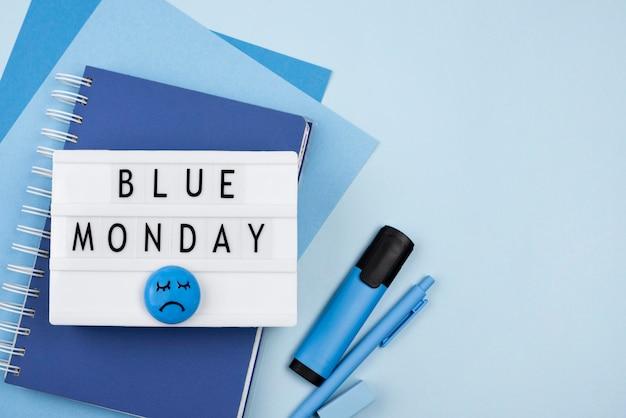 Vista superior de la caja de luz azul del lunes con cara triste y cuaderno