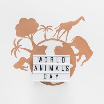 Vista superior de la caja de luz con planeta de papel y animales para el día de los animales.