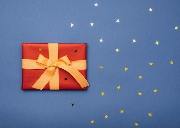 Vista superior de la caja de navidad con estrellas doradas y cinta