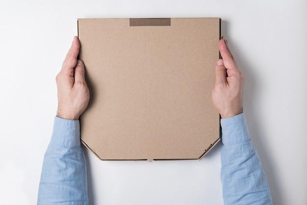 Vista superior en caja de pizza en manos masculinas. fondo blanco. concepto de entrega de alimentos a domicilio.